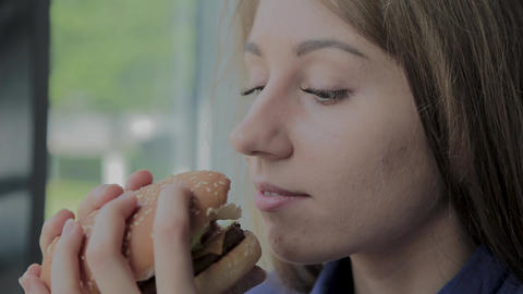 Beautiful girl eats a burger. Fast food restaurant Live Action