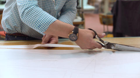 Tailor cutting out the marked pattern on fabric with large scissors on the Live Action