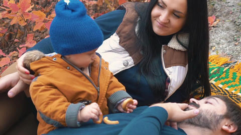Slow Motion Family Resting On Ground, Autumn Season, Fallen Leaves, Care Live Action