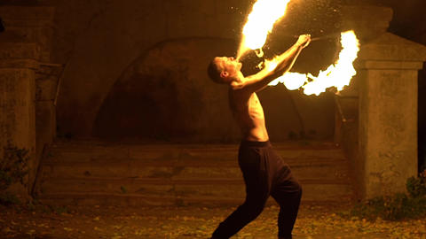 Slow Motion Fire Show Performance. Male Fire Performer Doing Fire Breathing Live Action