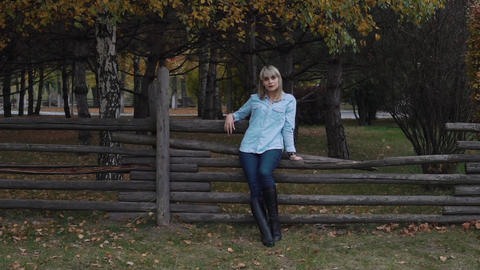 Real Time Happy Young Woman Enjoying Autumn Sitting On Wooden Fence Footage