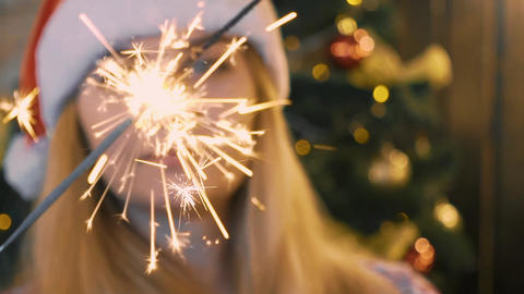Beautiful Girl Near Christmas Tree Holding Sparkler, Bengal Fire. Celebrating Footage