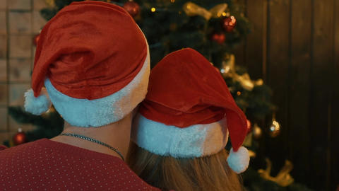 Real Time Couple In Santa Claus Hats Laying In Front Of The Christmas Tree Footage