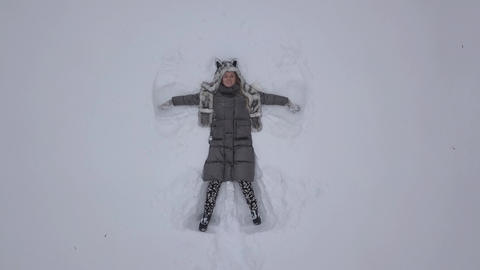 4K Woman Making Snow Angel Lying In Pure White Snow Footage