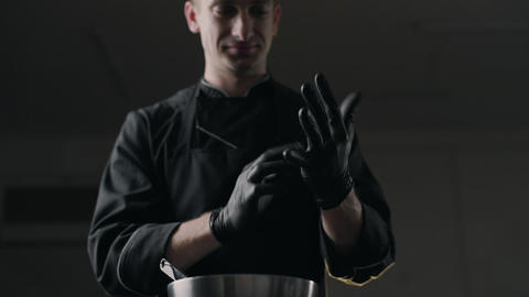 Chocolatier puts on the black rubber gloves, making of sweets and handmade Live Action