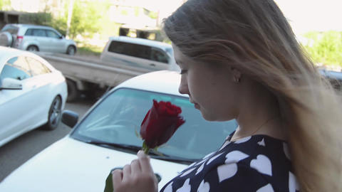Cute girl with a rose walking in the city center Footage