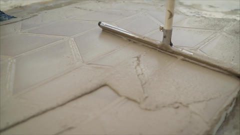 Mop clean pavement tiles.. The master tile smears the mucilage solution on the Footage