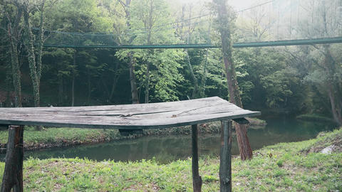 A walking bridge across the river in the mountain. The old wooden desk in front Footage