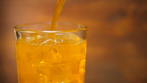 Orange Lemonade Pouring into Cold Glass with Ice Cube Footage
