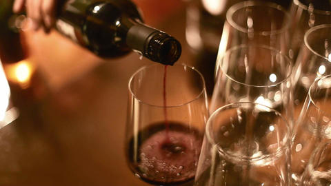 closeup pouring red wine with many glasses Footage
