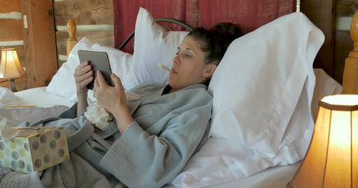 Young sick woman with a cough and fever talking to a doctor with her tablet during a video chat Footage