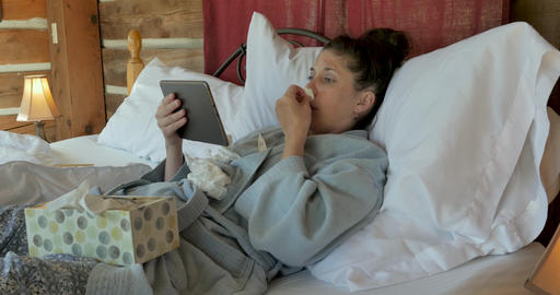 Woman with a cough and runny nose video chatting with a tablet in bed talking to a medical GIF