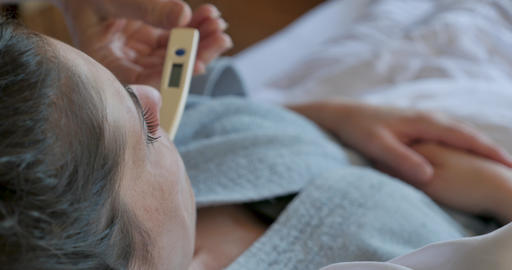 Close up of a hand taking a temperature of a woman lying in bed with a digital thermometer and then GIF