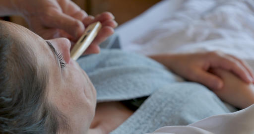 Close up of a hand removing a digital thermometer from a woman's mouth while she lies in bed in a Footage