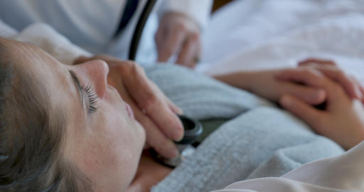 Close up of a doctor or nurse listening to the chest of a sick young woman lying in bed Footage