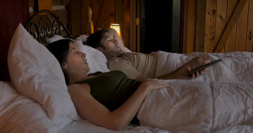 Attractive woman takes a TV remote from a man while watching television in bed - dolly shot Footage