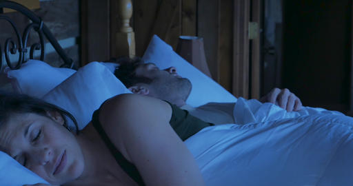 Happy woman lying on her side smiling in a comfortable bed with a man next to her at night GIF