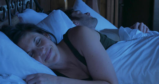 Attractive woman going to sleep with a smile on her face content, and relaxed next to a man lying in GIF
