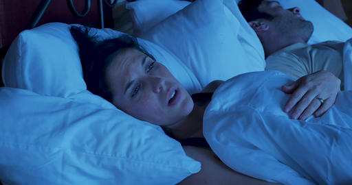 Young mother or wife, or girlfriend lying awake in bed at night unable to sleep worried and GIF