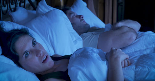 Married couple lying in bed angry at each other frowning and crossing their arms at not talking to Footage