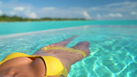 Sexy bikini body woman relaxing swimming in luxury infinity pool of resort Live Action