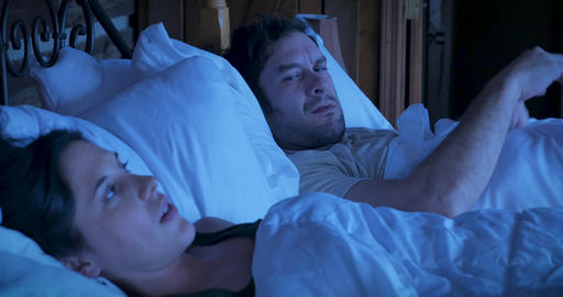 Man and woman with relationship troubles angry at each other while lying in bed at night GIF