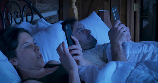 Young man and woman in their early 30s lying in bed looking at their mobile phone and digital tablet GIF