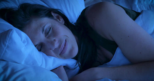 Close up of an attractive woman smiling while sleeping at night having good dreams or a comfortable Live Action