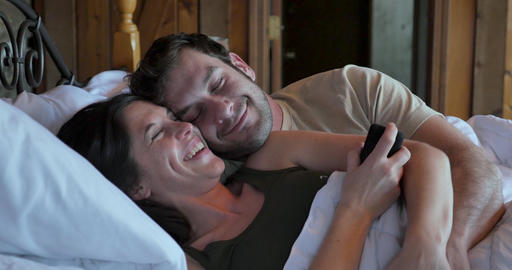 Handsome man and young beautiful woman in love laughing, smiling, and embracing in bed while holding Live Action