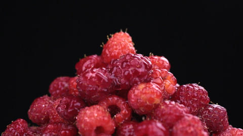 Raindrops fall on a rotating pile of ripe raspberries. Isolated Footage