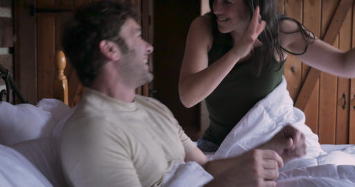 Attractive man and young woman happy dancing with each other celebrating life in bed in the morning GIF