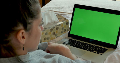 Sick young woman blowing her nose and coughing with a green screen computer on her lap nodding her GIF