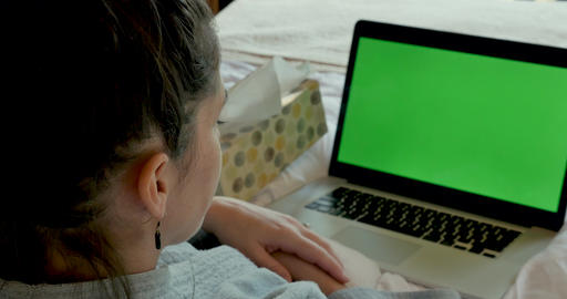 Sick young woman talking to a green screen computer while blowing her nose and lying in bed as if Footage