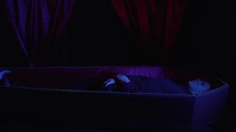 A man in the coffin is scratching his privates, dark blue lighting, 4k Live Action