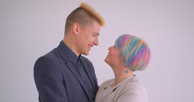 Millenial caucasian couple hugging tenderly on white background smiling into Footage