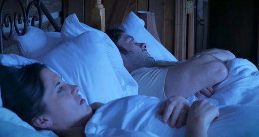 Attractive young woman and man arguing while lying in bed sighing and acting stubborn refusing to GIF