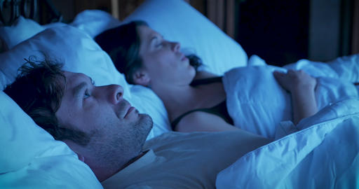 Man tossing and turning in bed unable to sleep expressing extreme frustration over his insomnia and Footage