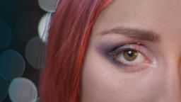 Closeup half face portrait of young attractive female with red dyed hair looking Footage