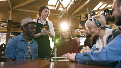 Young attractive waitress taking order from group of multi ethnic friends Live Action