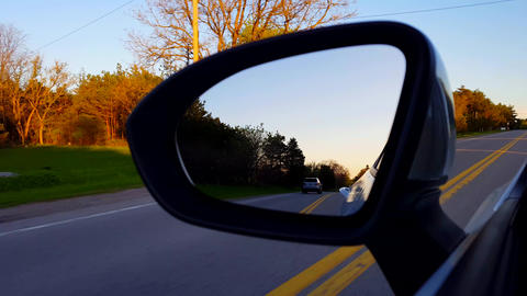 Driving Rural Road View of Side Mirror at Sunset. Driver Point of View POV Looking Down Side View Live Action
