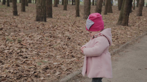 Beautiful little girl walks alone in the park Footage