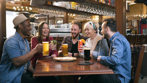 Company of young happy friends clinking glasses with beer and cocktails in bar Footage