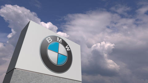 Logo of BMW on a stand against cloudy sky, editorial animation Live Action