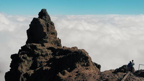Aerial view. A young couple stands on the edge of the cliffs above the clouds Footage