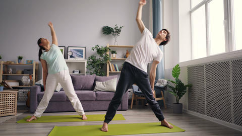 Mixed race young man doing yoga with Caucasian wife at home focused on training Footage
