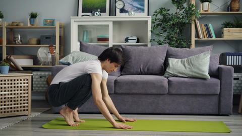 Handsome Asian guy doing headstand during yoga practice at home alone Footage