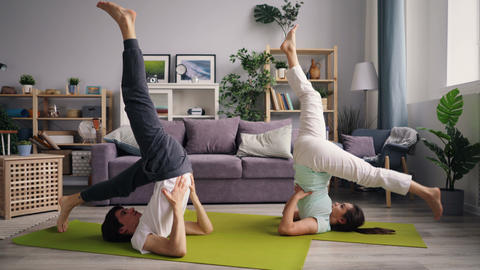 Man and woman doing sequence of yoga asanas in inverted position at home Footage