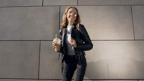 Attractive young woman in a white T-shirt and jacket holding milkshake while Live Action