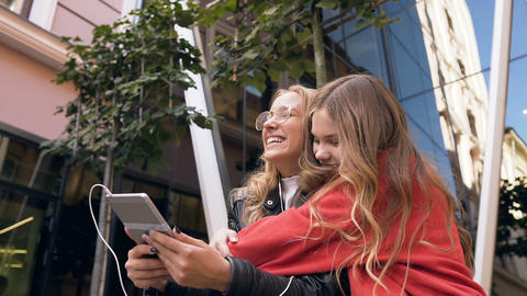 Two women friends using digital tablet in outdoors. Smiling girl friends looking Live Action
