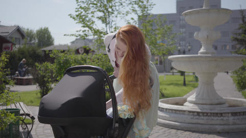 Beautiful red-haired woman bent over a pram and smiling in the park. The lady Live Action